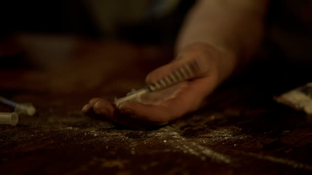 Hand of male opiate addict under influence falling on table, drug abuse problem video
