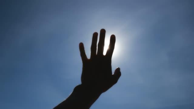 vídeos de stock e filmes b-roll de hand of man and deep blue sky. - retroiluminado