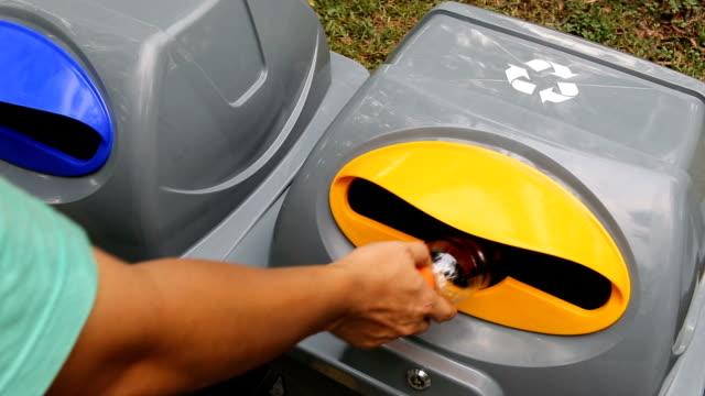 hand des mannes führen ein kunststoff-flasche in farbe müll zu entsorgen. - altglas stock-videos und b-roll-filmmaterial
