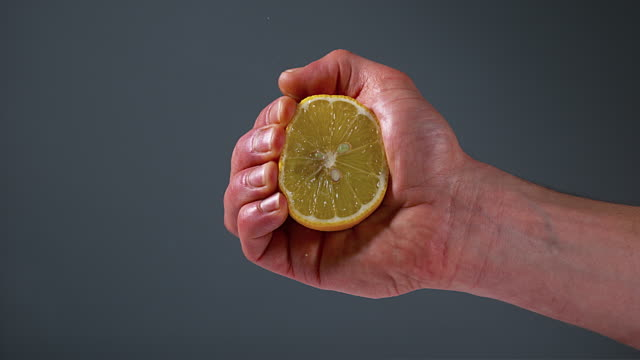 Hand of Man Squeezing Lemon, citrus limonum against Black Background, Slow Motion 4K video