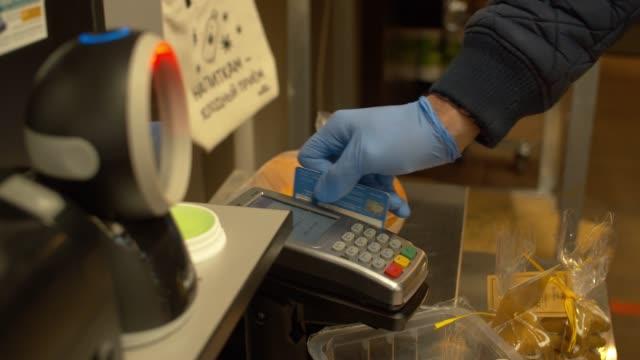 hand of man swiping card on cash machine - rękawiczka filmów i materiałów b-roll