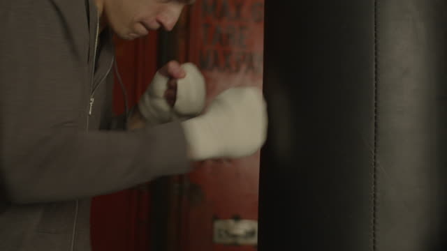hand of motivated boxer hitting punching bag in gym - sacco per il pugilato video stock e b–roll