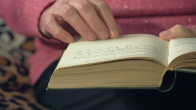 Hand av gammal kvinna vända sidor av boken när man läser den på nära håll. Filmiskt ljus hemma eller i biblioteket video