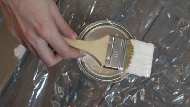 hand des malers eintauchen einen pinsel in einen eimer mit weißer farbe, slow-motion - eimer stock-videos und b-roll-filmmaterial