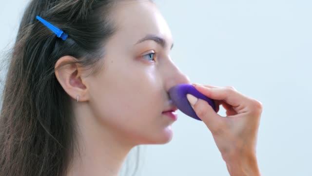 vídeos de stock e filmes b-roll de hand of professional make-up artist applying tonal cream or remedy using sponge - esponja