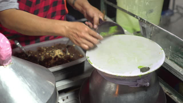 Hand of Thai chef cooking Local street food, Thai steamed rice, and pandan-skin dumpling with deep-fried garlic and chili at the local walking street at Nan, one of the famous travel destinations to go to at night, Thailand.