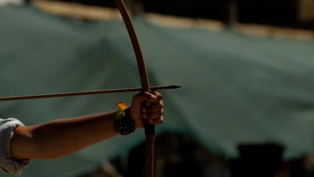 vidéos et rushes de main de l'archer tire les cordes d'arc sur la proue - tir à l'arc
