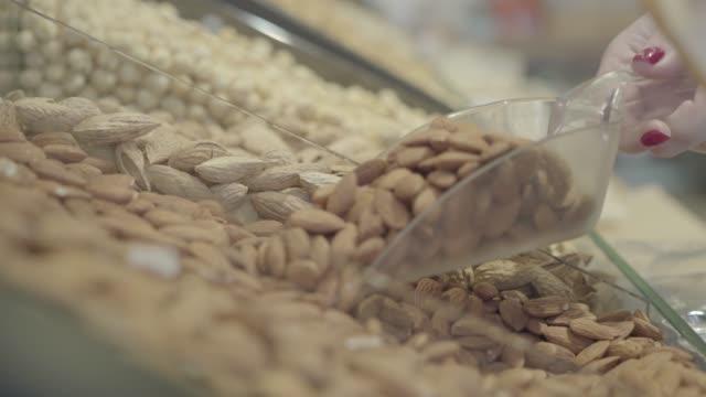 hand von nicht wiederzuerkennen kaukasischen frau, die gesunde nüsse aus lebensmittelregal. unbekannte kundin pflücken rohe mandeln im supermarkt. gesunde ernährung, lebensstil, vegetarismus. s-log 2. - handvoll stock-videos und b-roll-filmmaterial