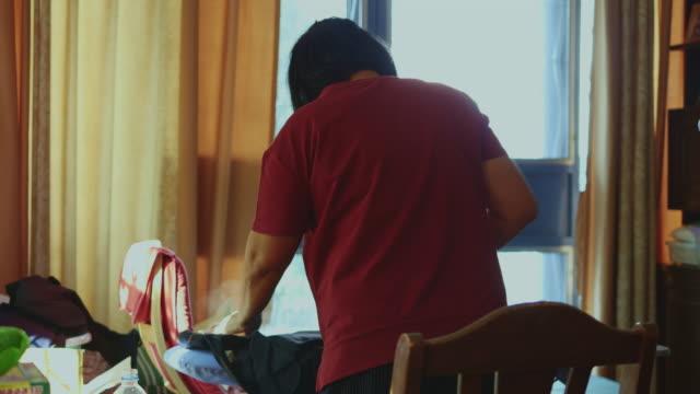 stockvideo's en b-roll-footage met hand van vrouw strijken kleren op de tafel - alleenstaande moeder