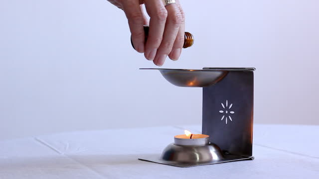 vídeos de stock e filmes b-roll de hand of woman pouring essential oil into silver diffuser with candle underneath over white background - aromaterapia