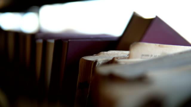 stockvideo's en b-roll-footage met hand van de vrouw het selecteren van een boek uit boekenplank - boekenkast
