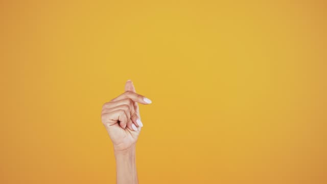 Hand of woman snapping fingers over orange background Hand of a female is snapping fingers against orange studio background. Copy space for your text or image. Advertising area, mock up. Close up, slow motion snapping stock videos & royalty-free footage