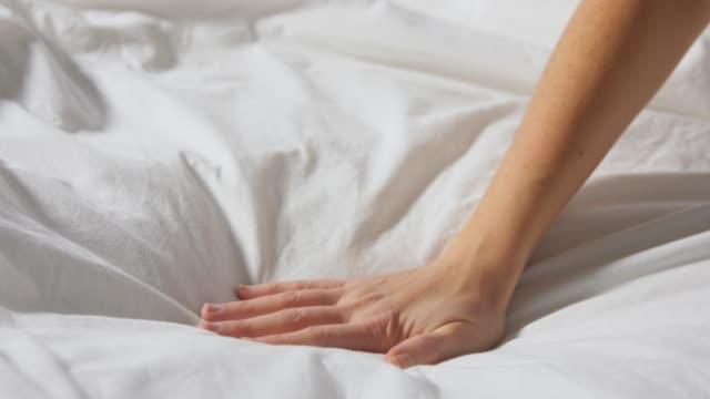 vídeos y material grabado en eventos de stock de mano de la mujer tocando la cama cubierta con manta - colchón
