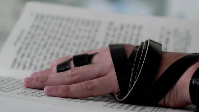 Hand of young jewish man with a tefillin on his arm, holding a psalms book. video