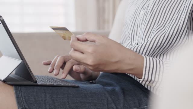 hand of young women are buying online with credit card while sitting on sofa. woman are using tablet and doing online transactions. - credit card filmów i materiałów b-roll