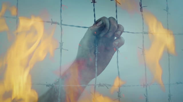 Hand On Fence With Smoke And Fire