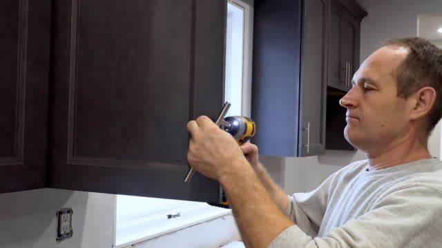 Hand on handle installation of door handles on opening cabinet door in kitchen with a screwdriver Hand on handle installation of door handles on opening cabinet door in kitchen with a screwdriver cabinet stock videos & royalty-free footage
