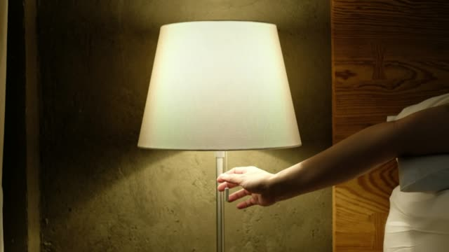 Hand open and close  head lamp near bed in bedroom