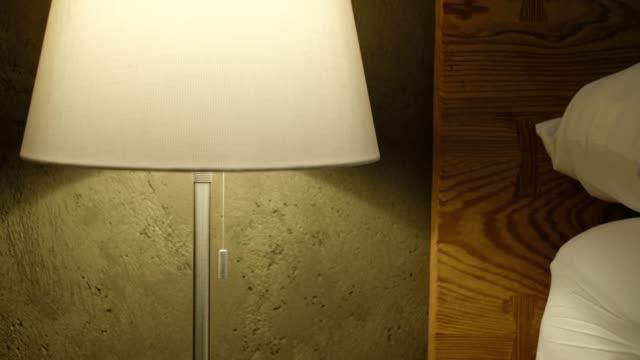 hand öffnen und schließen der stirnlampe in der nähe von bett im schlafzimmer - elektrische lampe stock-videos und b-roll-filmmaterial