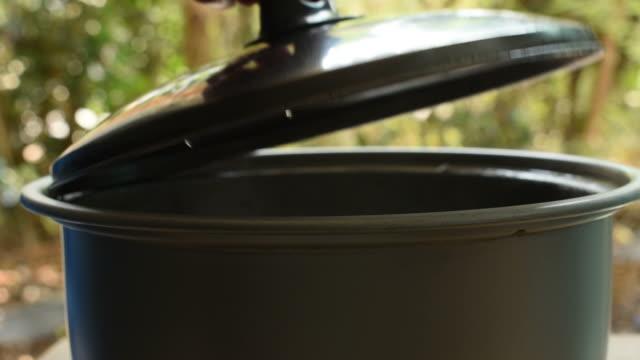 vídeos y material grabado en eventos de stock de abra la tapa de la olla olla arrocera eléctrica de la mano y el humo flotando - gastronomía fina