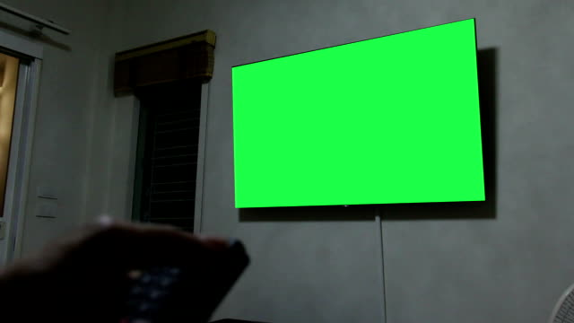 hand open smart TV via remote control with green screen monitor TV video