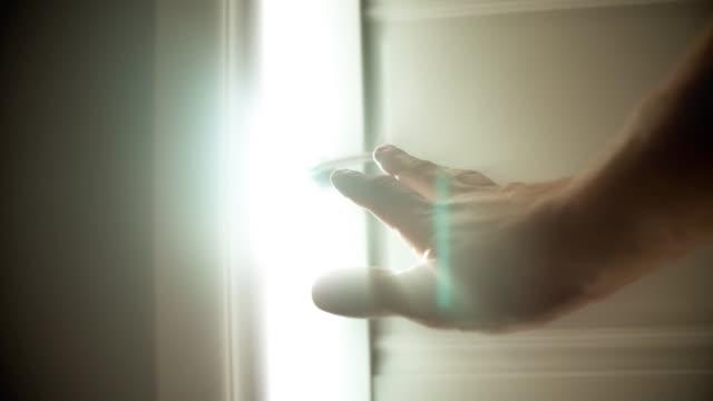 Hand opening door to a bright light.