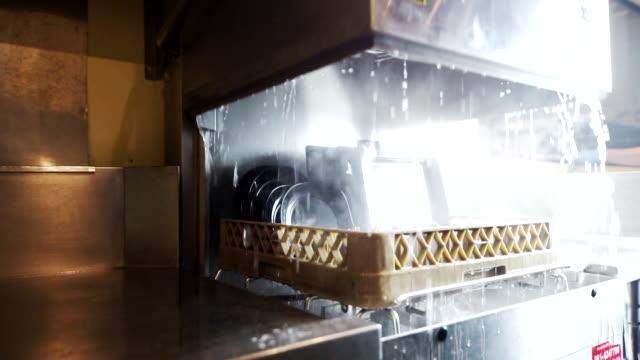 handöffnen der spülmaschine nach dem reinigungsprozess. - essgeschirr stock-videos und b-roll-filmmaterial