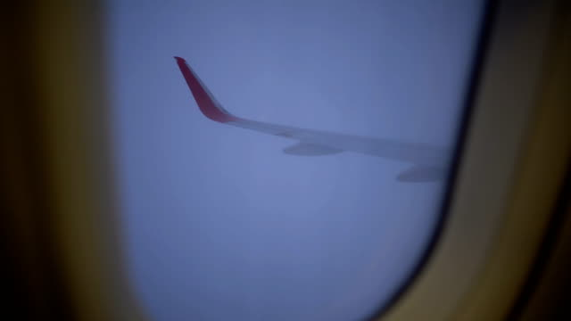 Hand opening the plane window during a flight with heavy cloud. video