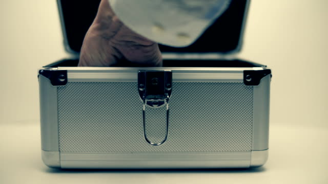 Hand opens a metallic suitcase and trying to find money inside, but empty