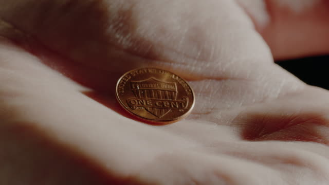 A hand opens revealing an extreme close up of an American penny.  At the end, the hand then closes around it for safe keeping. The hand is hanging on to the penny tightly. us coin stock videos & royalty-free footage