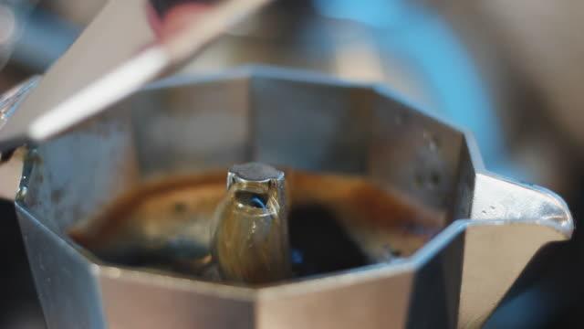 hand opens the moka pot with boiling coffee, process of making coffee, close-up shot - cucina italiana video stock e b–roll
