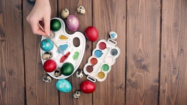 рука окрашены пасхальные яйца, краски и кисти на деревянном фоне. подготовка к празднику. девушки руки рисуют шаблон - white background стоковые видео и кадры b-roll