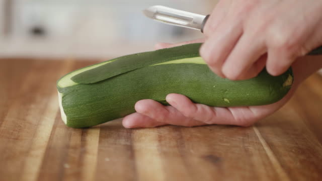 hand peeling courgette ribbon for summer salad - zucchini video stock e b–roll