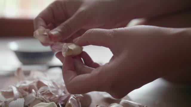 Hand peeling garlic on wooden chopping board