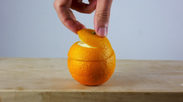 Hand peels an orange easily on wooden cutting board. 4K Ultra HD. Skin care concept.