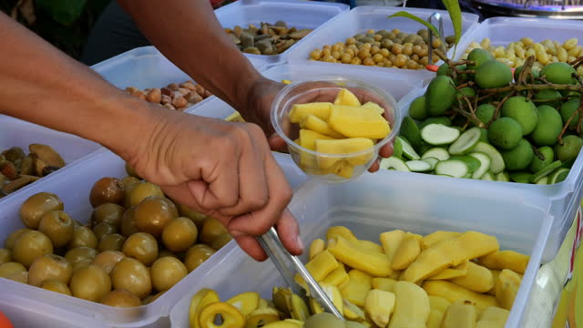 Hand pick up pickled fruit for customer,street food in Thailand