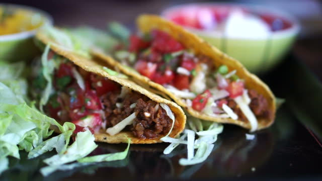 Hand picking taco to plate. Delicious Mexican food experience with minced meat and salsa video