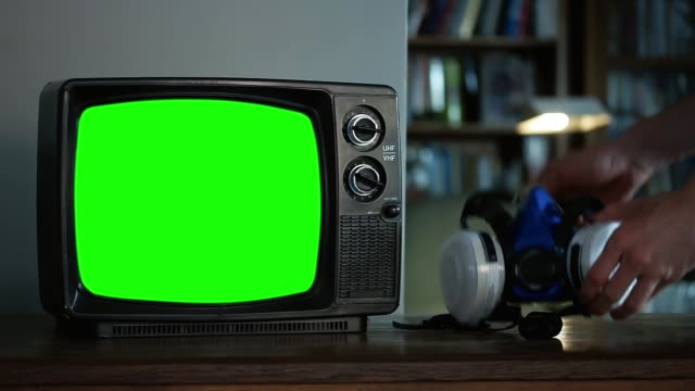 """Hand picking up a Face Respirator Mask and a Retro TV with Green Screen. Close-Up. You can Replace Green Screen with the Footage or Picture you Want with """"Keying"""" effect in After Effects."""