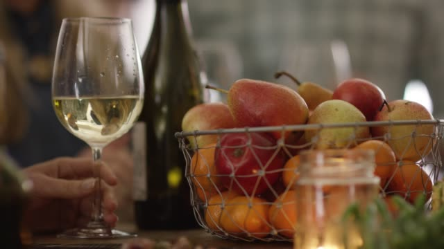 Hand picking up a white wine glass near a basket of fruit and a lit candle video