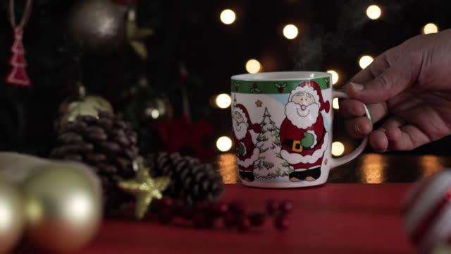 vídeos de stock, filmes e b-roll de mão pegando caneca de natal - chocolate quente