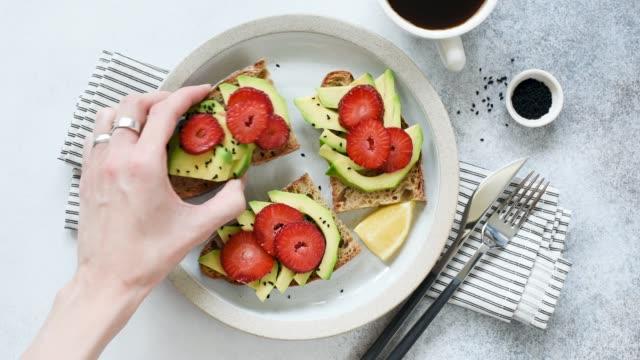 stockvideo's en b-roll-footage met hand picks toast met avocado - geroosterd brood