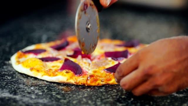 vídeos y material grabado en eventos de stock de pizzera de mano corte pizza horneada en la pieza sobre la mesa de la cocina en pizzeria - gastronomía fina