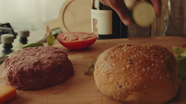vídeos de stock e filmes b-roll de a hand places a zucchini on a platter with a plant based, non-meat, vegan burger - meat texture