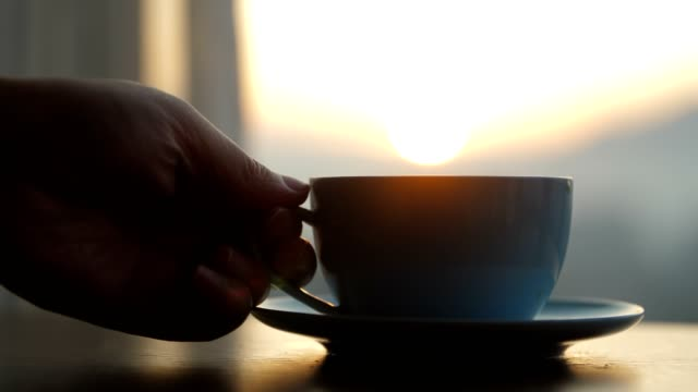 Hand placing hot coffee cup