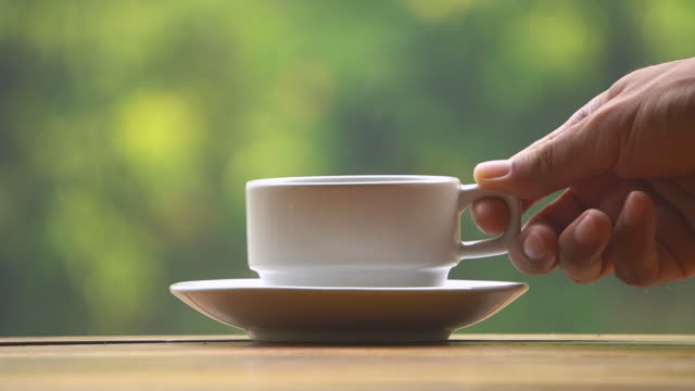 Hand placing hot coffee cup with smoke on saucer Close-up of hand placing hot ceramic white coffee cup with smoke on saucer over wooden table in nature green background mug stock videos & royalty-free footage