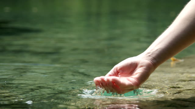 SLOW MOTION CLOSE UP: Hand playing with clear fresh water in beautiful mountain lake video