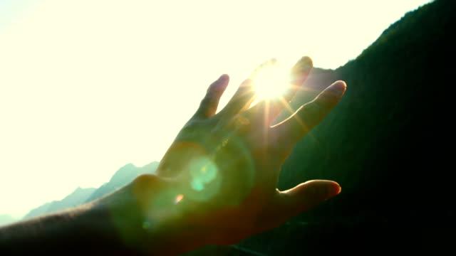 vídeos de stock, filmes e b-roll de mão brincando com luz solar - mão