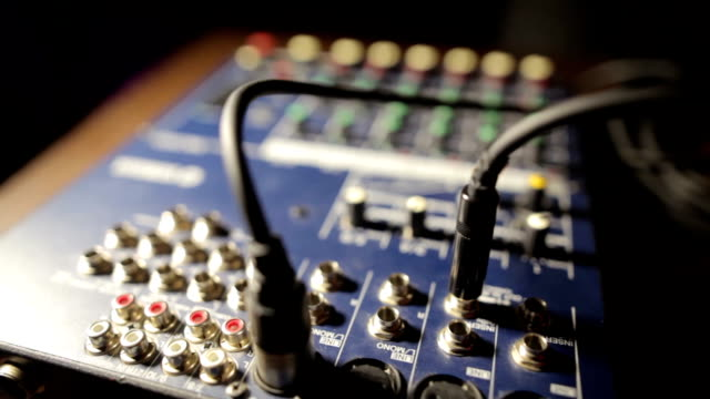 Hand plugging a jack in sound mixer video