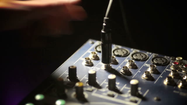 Hand plugging jack in mixer video