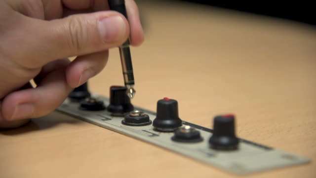 a hand plugging off the jack of an earphone into a studio of a radio station - cavo d'acciaio video stock e b–roll